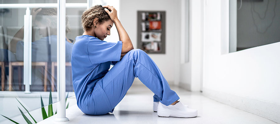 nurse sitting on floor with head in hands