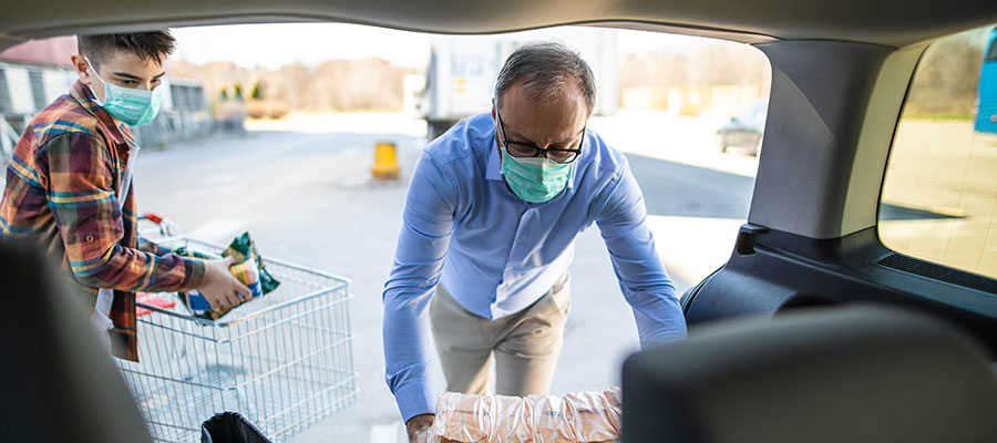 people with masks loading groceries into car